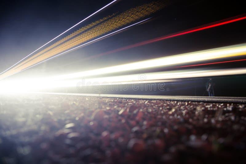 Schönes, abstraktes Auto beleuchtet auf einer Landstraße Handeln Sie in der Nacht und von einem Straßenrand schauen stockfotos