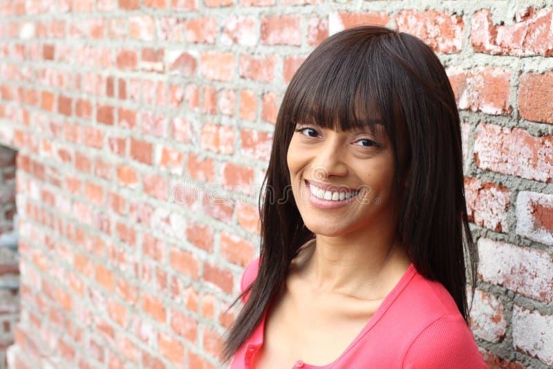 Schönes Afroamerikanermädchen betrachtet Kamera und lächelt bei der Stellung gegen Wand des roten Backsteins stockfotos