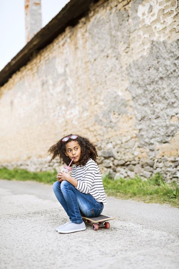 Schönes Afroamerikanermädchen, das auf Skateboard, trinkender Saft sitzt lizenzfreies stockbild