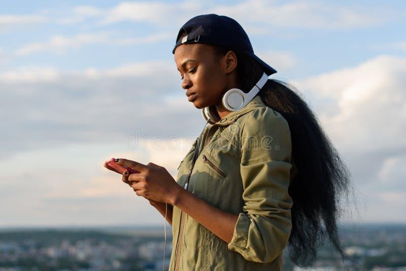 Schönes Afroamerikanermädchen hören Musik und genießen Lächelnde junge schwarze Frau auf unscharfem Stadthintergrund stockfoto