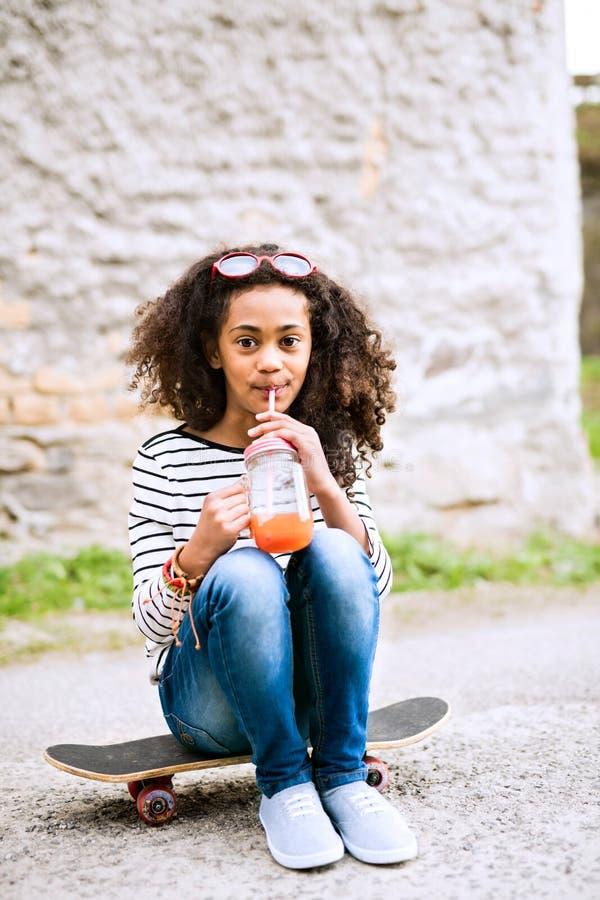 Schönes Afroamerikanermädchen mit dem Glas und Stroh, trinkend lizenzfreies stockfoto