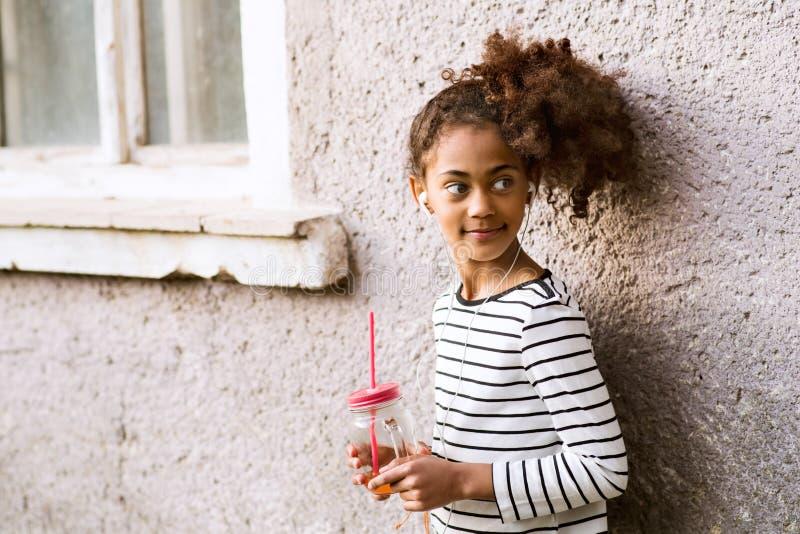 Schönes Afroamerikanermädchen mit dem Glas und Stroh, trinkend stockfotos