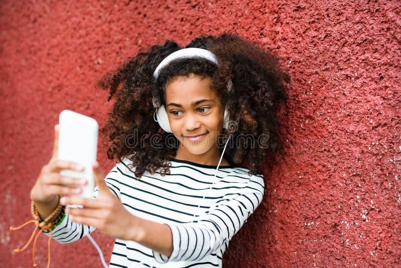 Schönes Afroamerikanermädchen mit dem intelligenten Telefon, das selfie nimmt stockfoto