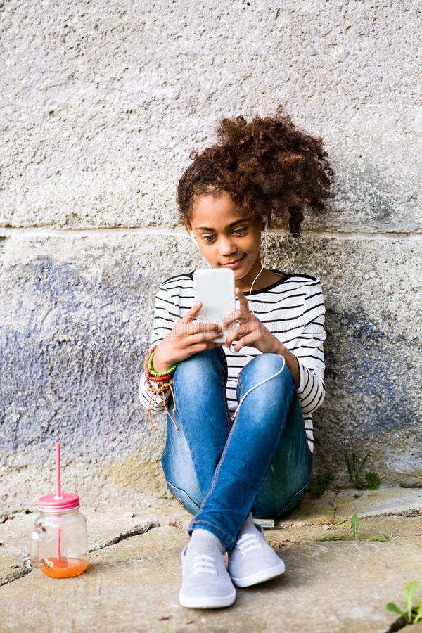 Schönes Afroamerikanermädchen mit intelligentem Telefon und Getränk lizenzfreie stockbilder