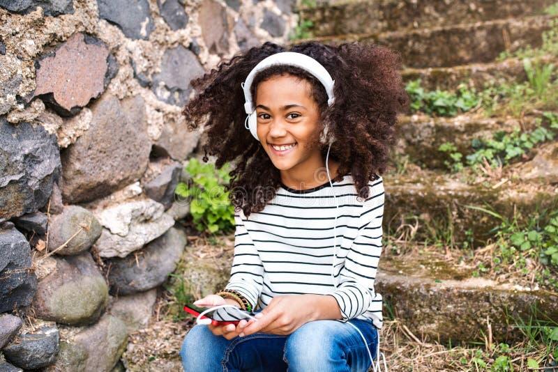Schönes Afroamerikanermädchen mit intelligentem Telefon und Kopfhörern lizenzfreie stockfotos
