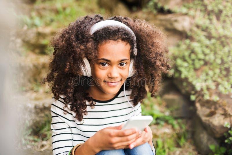 Schönes Afroamerikanermädchen mit intelligentem Telefon und Kopfhörern stockfotografie