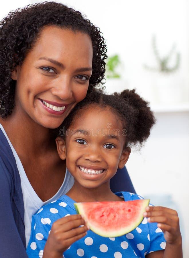 Schönes afroes-amerikanisch Mädchen, das Wassermelone isst lizenzfreie stockfotos