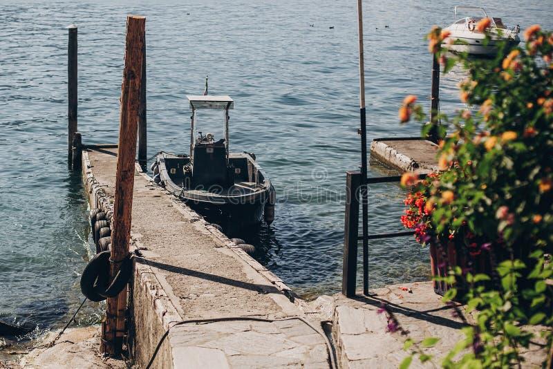 Schönes altes Dock mit gealterten hölzernen Spalten und Boot auf Ufer von Lago Maggiore auf Borromean-Inseln nahe Stresa-Stadt, I lizenzfreie stockfotos