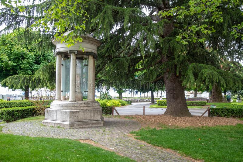 Schönes altes Steinmonument mit großem üppigem grünem Park des Baums öffentlich, Lausanne lizenzfreies stockbild
