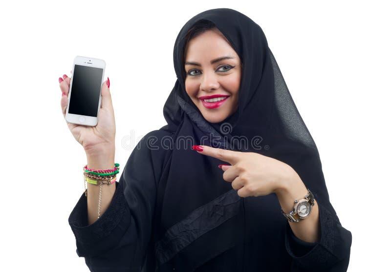 Schönes arabisches Modell, das einen Handy auf einem lokalisierten Hintergrund hält stockbild