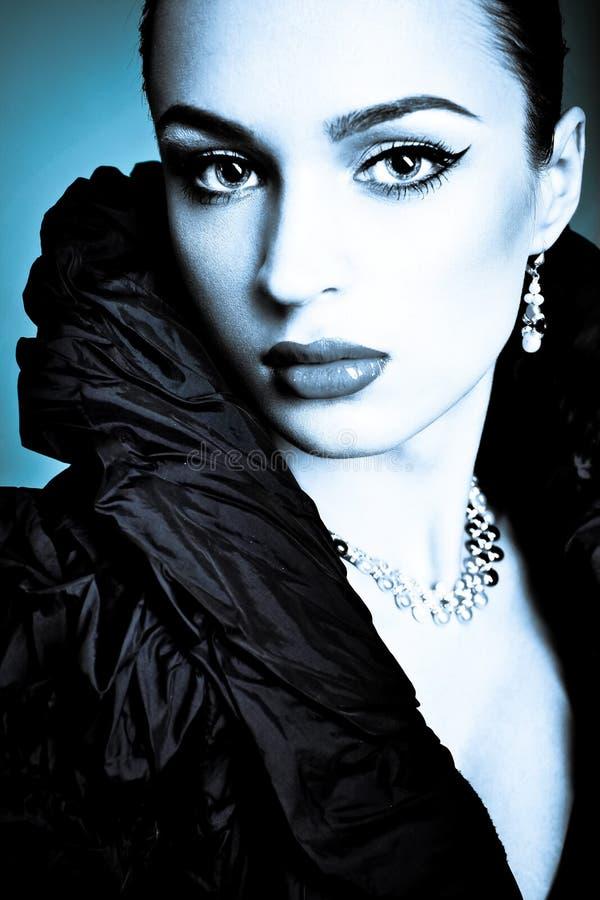 Schönes Art und Weisemädchen auf dem blauen Hintergrund stockbild