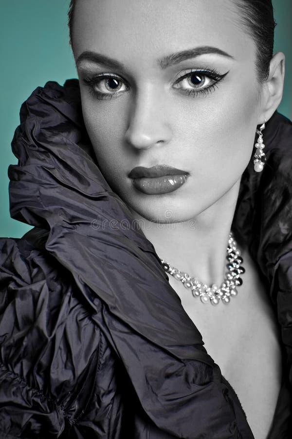 Schönes Art und Weisemädchen auf dem Türkishintergrund lizenzfreies stockbild