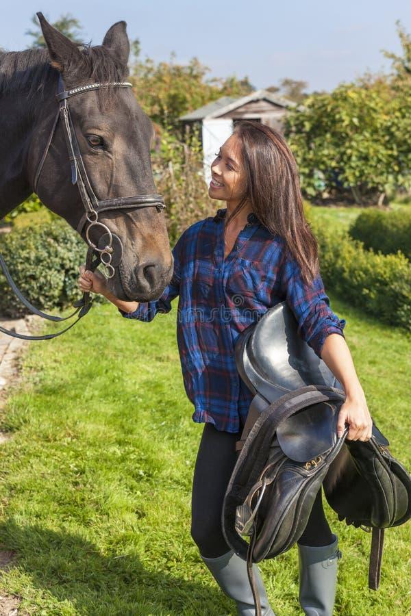 Schönes asiatisches eurasisches Mädchen mit ihrem Pferd stockbilder