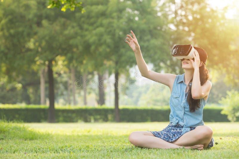 Schönes asiatisches Frauennote scrrn mit VR-Kopfhörer lizenzfreie stockfotografie