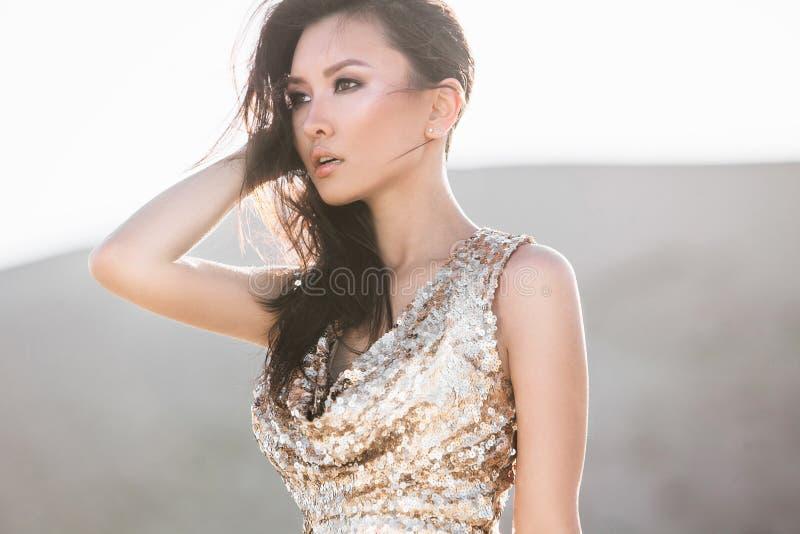 Schönes asiatisches glänzendes Luxuskleid der Frau in Mode in der Wüste stockfoto