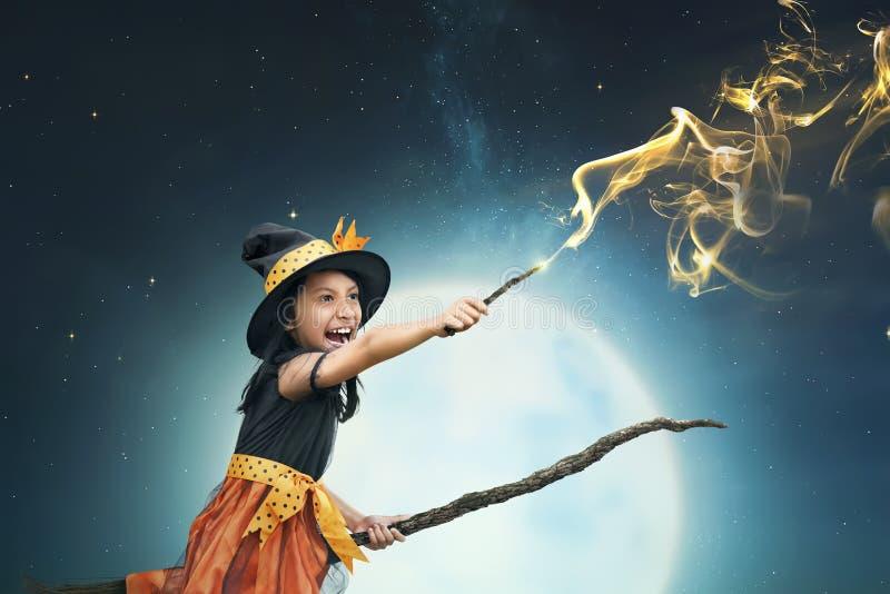 Schönes asiatisches Hexenmädchen, das den magischen Stab verwendet lizenzfreie stockfotos