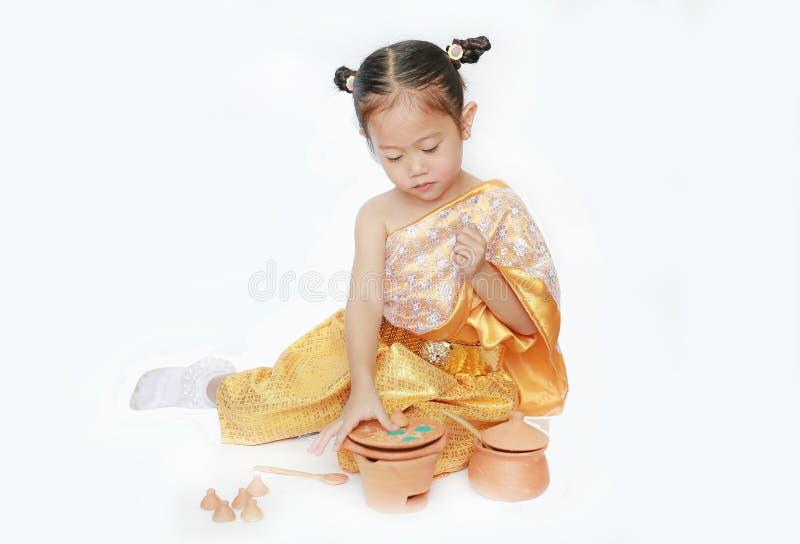 Schönes asiatisches Kindermädchen im traditionellen thailändischen Kleiderspiel, das den thailändischen Kulturnachtisch lokalisie lizenzfreie stockfotografie