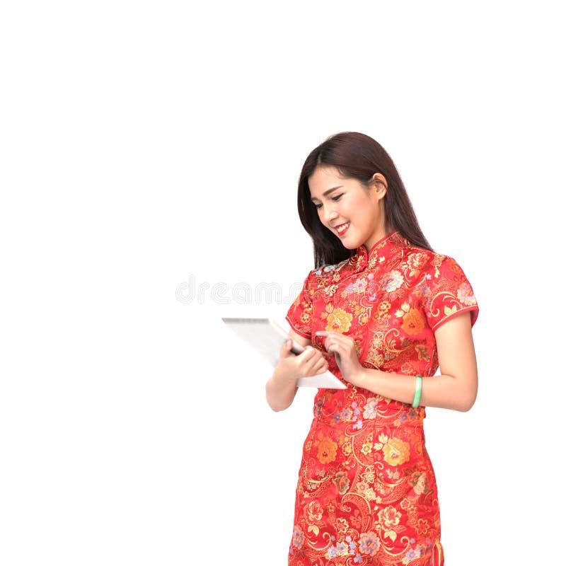 Schönes asiatisches Mädchen in chinesischem qipao Trachtenkleid unter Verwendung der digitalen Tablette, im chinesischen neuen Ja lizenzfreie stockbilder