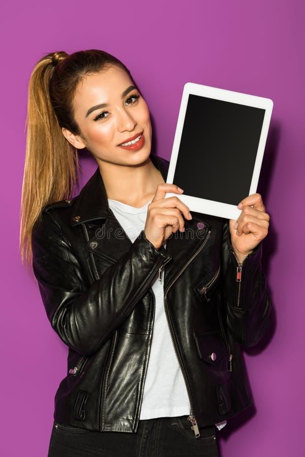 schönes asiatisches Mädchen, das digitale Tablette mit leerem Bildschirm hält und an der Kamera lächelt lizenzfreies stockfoto