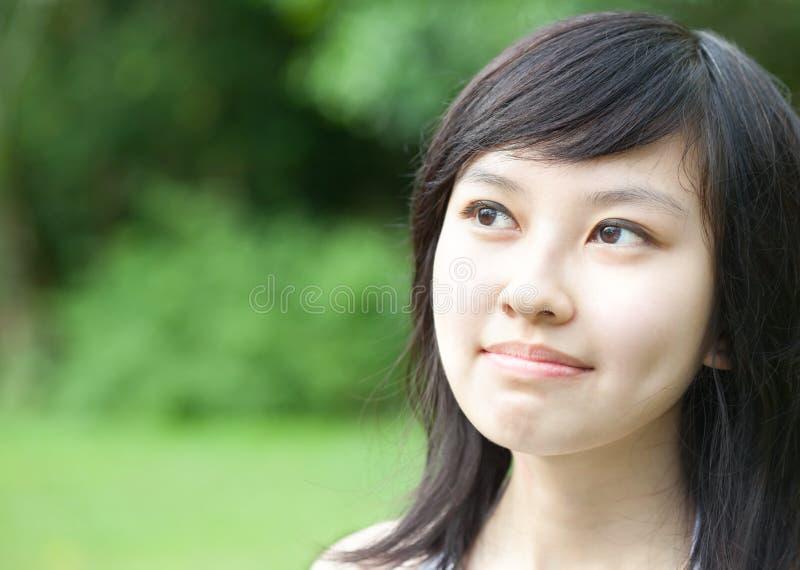 Schönes asiatisches Mädchen, das draußen lacht stockfotografie