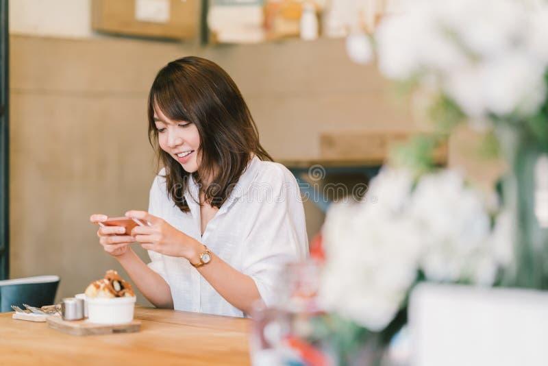 Schönes asiatisches Mädchen, das Foto von Süßspeisen an der Kaffeestube, unter Verwendung der Smartphonekamera, gebend auf Social stockbild