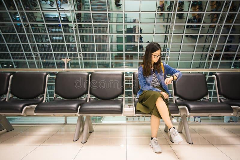 Schönes asiatisches Mädchen, das ihre Uhr, wartend, um Flugzeug, Zeitkonzept zu verschalen betrachtet lizenzfreie stockfotografie
