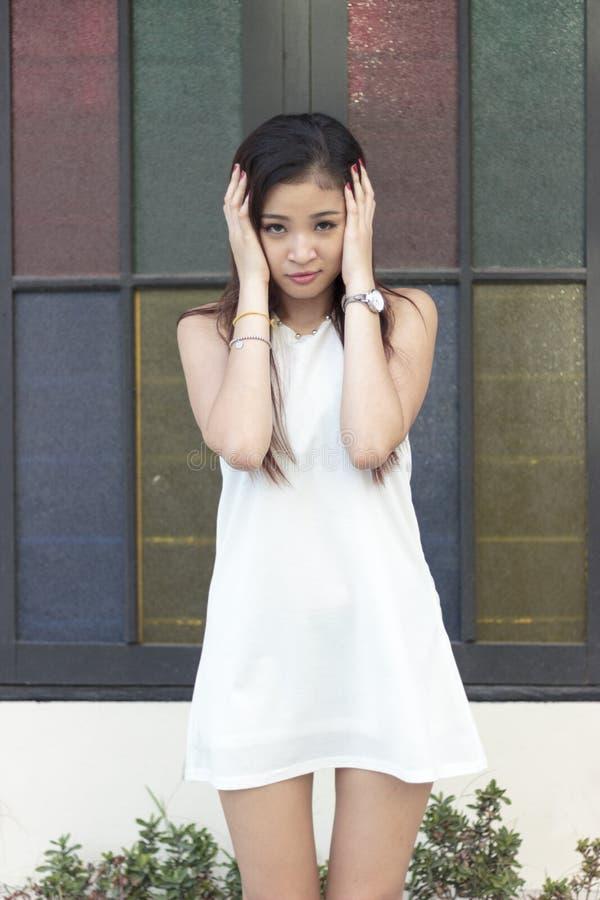 Schönes asiatisches Mädchen, das vor einem Fenster aufwirft stockfoto