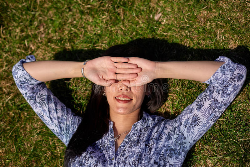 Schönes asiatisches Mädchen in einer blauen Bluse liegt auf einem grünen Gras und bedeckt ihr Gesicht mit ihren Händen lizenzfreie stockbilder