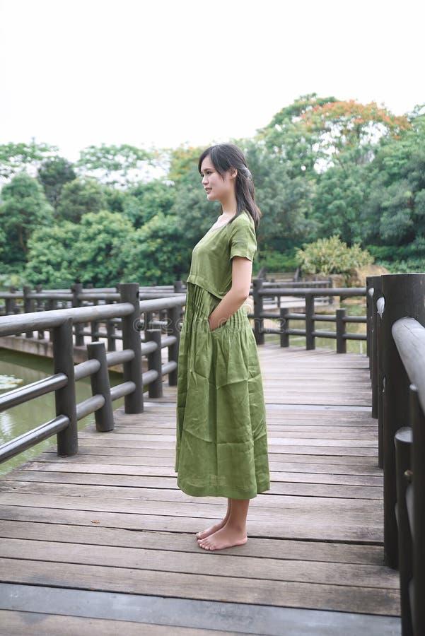 Schönes asiatisches Mädchen kleidete im traditionellen Elementkleid an, das sich zeigt lizenzfreies stockbild
