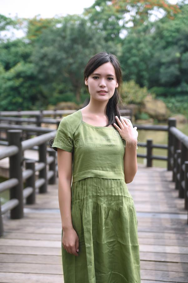 Schönes asiatisches Mädchen kleidete im traditionellen Elementkleid an, das sich zeigt lizenzfreie stockfotografie