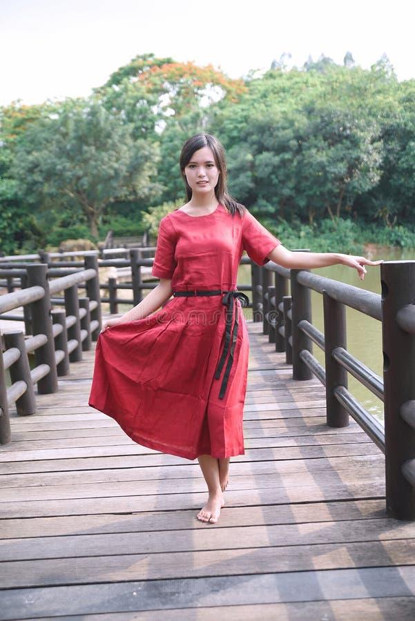 Schönes asiatisches Mädchen kleidete im traditionellen Elementkleid an, das sich zeigt stockfotos