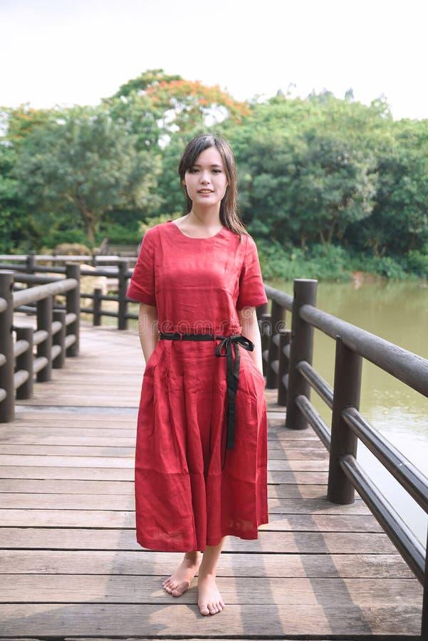 Schönes asiatisches Mädchen kleidete im traditionellen Elementkleid an, das sich zeigt stockfoto