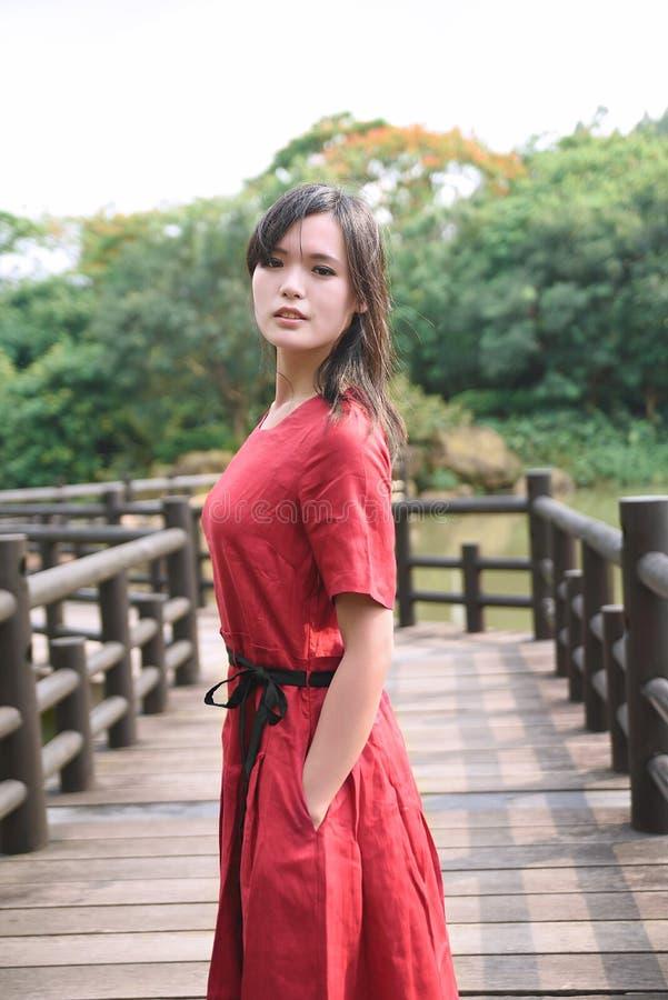 Schönes asiatisches Mädchen kleidete im traditionellen Elementkleid an, das sich zeigt stockbild