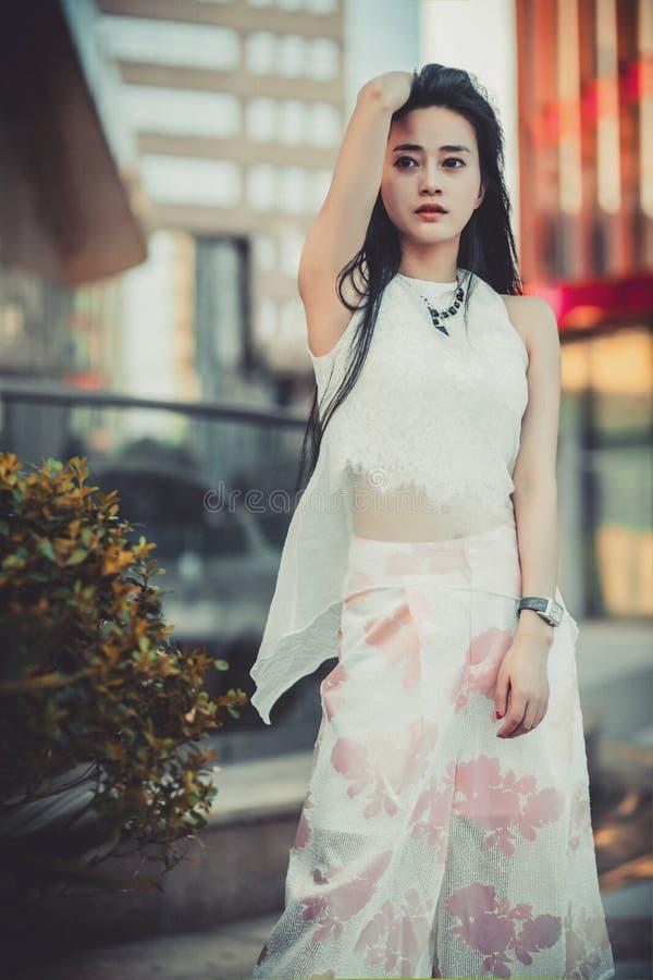 Schönes asiatisches Mädchenmodell im weißen Kleid, das am modernen Artstadt-Parkhintergrund aufwirft lizenzfreies stockbild