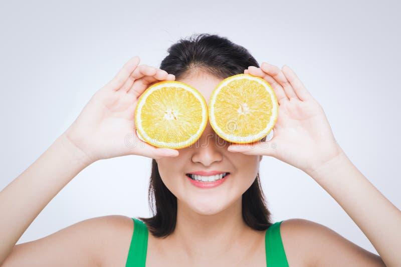 Schönes asiatisches Porträt der jungen Frau mit Orangen Gesundes Nahrungsmittelkonzept Hautpflege und Schönheit Vitamine und Mine lizenzfreie stockfotos