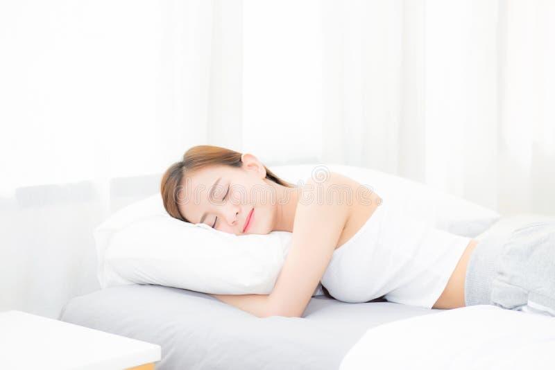 Schönes asiatisches Schlafenlügen der jungen Frau im Bett mit Kopf auf dem Kissen bequem und glücklich stockbild