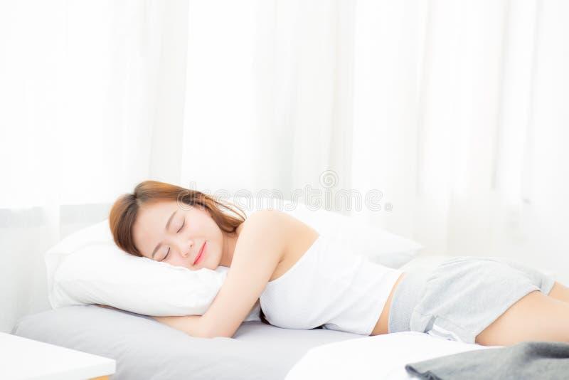 Schönes asiatisches Schlafenlügen der jungen Frau im Bett mit Kopf auf dem Kissen bequem und glücklich lizenzfreies stockfoto