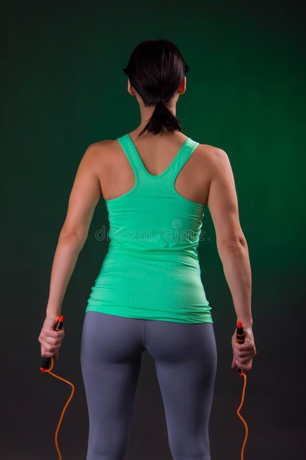 Schönes athletisches, Eignungsfrauenstellung, werfend mit einem Seilspringen auf einem grauen Hintergrund mit einer grünen Hinter stockfoto