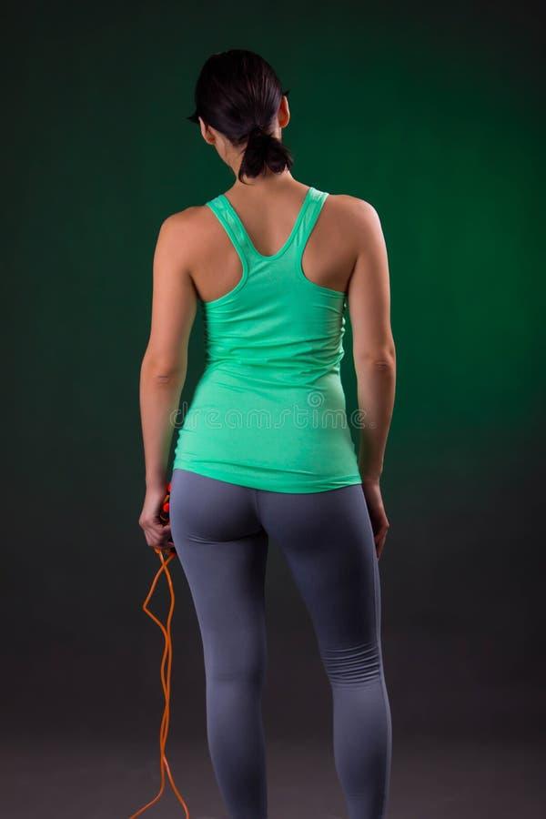 Schönes athletisches, Eignungsfrauenstellung, werfend mit einem Seilspringen auf einem grauen Hintergrund mit einer grünen Hinter stockbilder