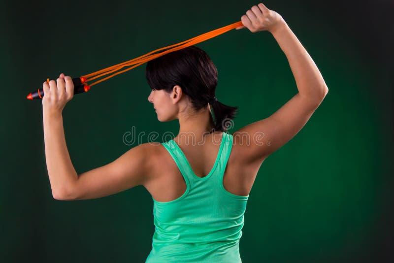 Schönes athletisches, Eignungsfrauenstellung, werfend mit einem Seilspringen auf einem grauen Hintergrund mit einer grünen Hinter lizenzfreie stockfotos