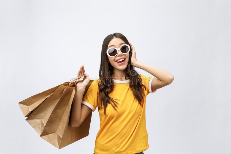 Schönes attraktives Asiatinlächeln und Halten des Einkaufstascheglaubens also des Glückes und mit schwarzem Freitag-Verkauf genie lizenzfreies stockbild