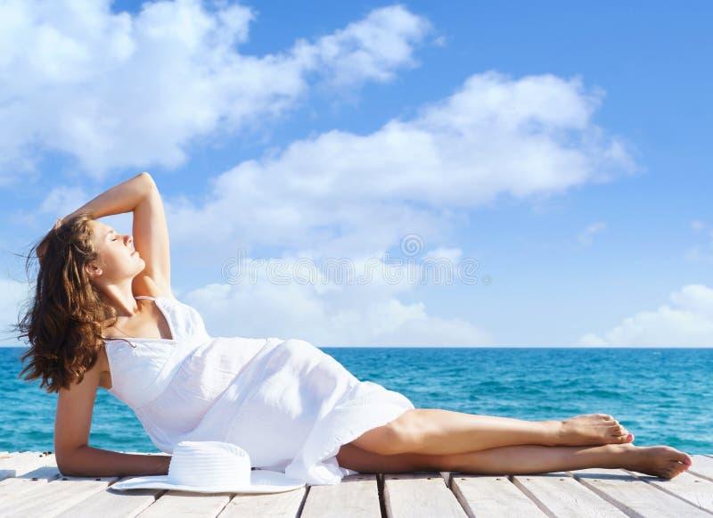 Schönes, attraktives Modell, das im weißen Kleid auf einem hölzernen PU aufwirft stockbild