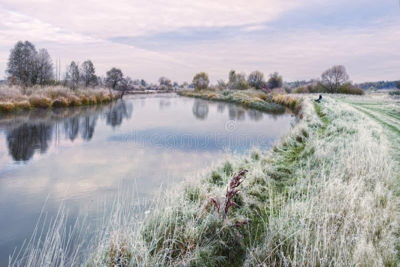 Schönes Autumn Belarusian Landscape On The-Thema des Fischens: Grasartige Bank einziger Fischer-Sits On Thes des Flusses, bedeckt stockbild