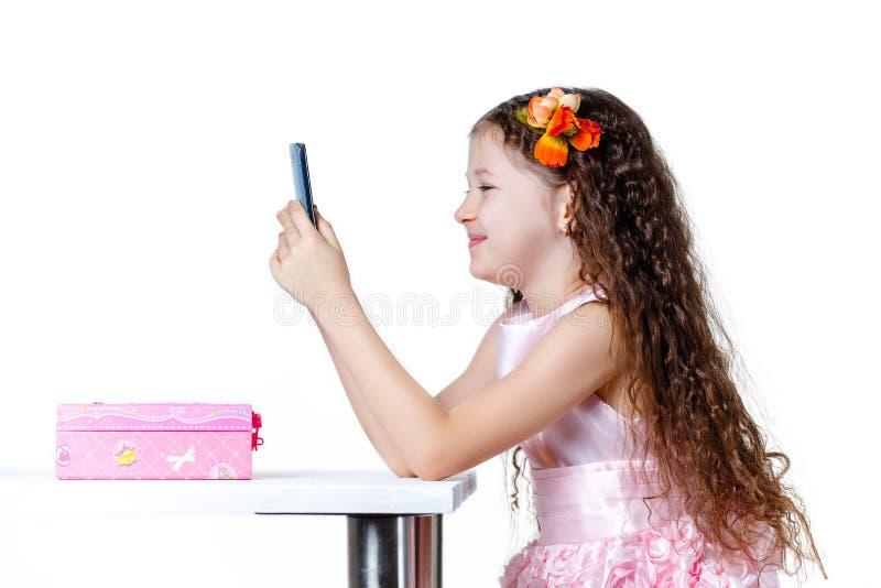 Schönes Baby, das am Telefon in einem Kleid lokalisiert auf einem weißen Hintergrund spricht stockfotografie