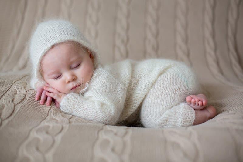 Schönes Baby im Weiß strickte die Stoffe und Hut und schlief stockfoto