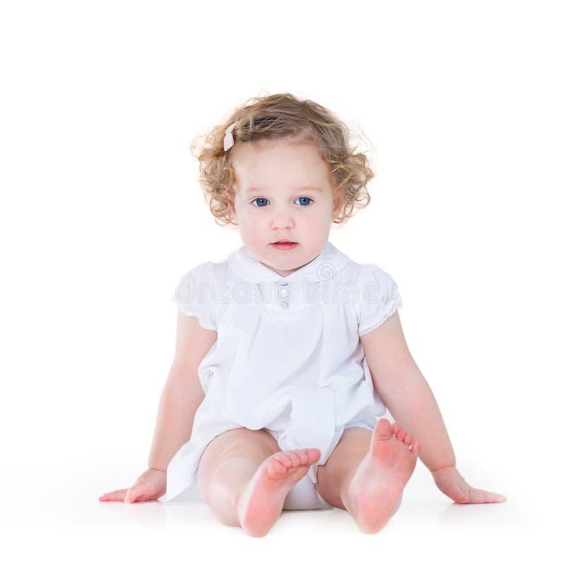 Schönes Baby mit dem gelockten Haar im netten weißen Kleid stockfotos