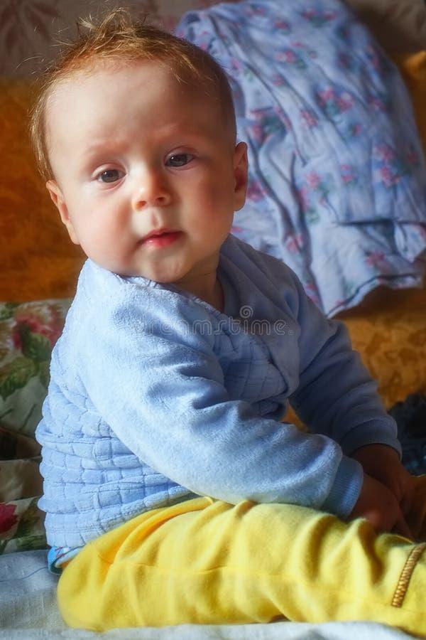 Schönes Baby zu Hause, das auf der Couch sitzt stockbild