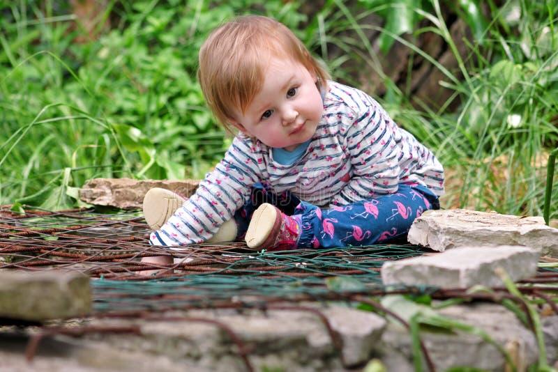 Schönes Babysitzen, lächelnd und werfen, Porträt auf Kleines nettes Mädchen ist im Garten spielerisch Kind spielt draußen im Park stockbild