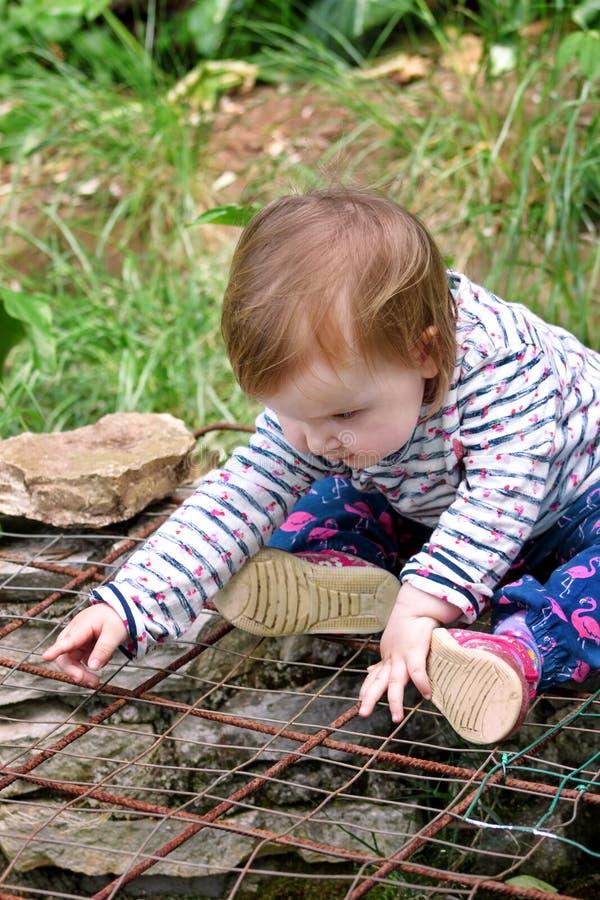 Schönes Babysitzen, lächelnd und werfen, Porträt auf Kleines nettes Mädchen ist im Garten spielerisch Kind spielt draußen im Park stockfotografie