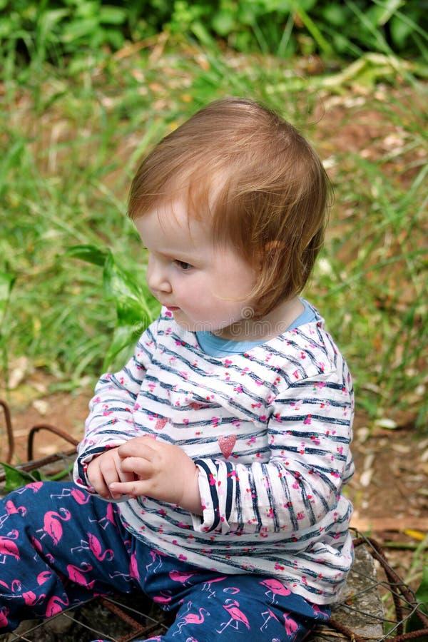 Schönes Babysitzen, lächelnd und werfen, Porträt auf Kleines nettes Mädchen ist im Garten spielerisch Kind spielt draußen im Park stockfotos